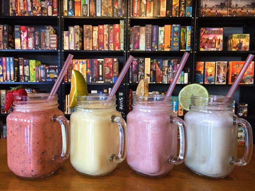 Nossos Smoothies refrescantes com iogurte, mel e frutas frescas, e, ao fundo, o acervo com cerca de 300 jogos de tabuleiro modernos